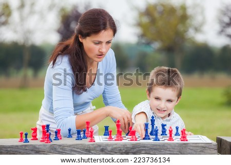 Elegant young boy in white shirt and his mother learning to play chess with blue and red chess pieces on wood table in the park  - stock photo