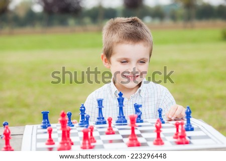 Elegant young boy in white shirt learning to play chess with blue and red chess pieces on wood table in the park  - stock photo