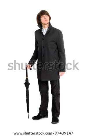 Elegant young business man in a raincoat looking up. - stock photo