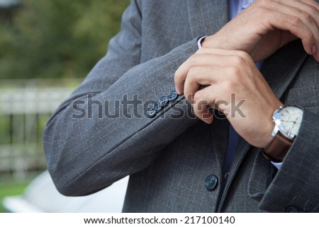 Elegant young business man in tuxedo buttoning the jacket - stock photo