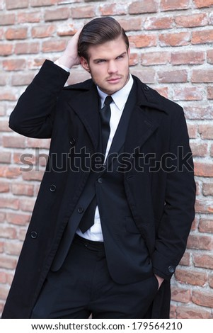 elegant young business man posing in front of a brick wall, arranging his hair and holding a hand in his pocket while looking away from the camera - stock photo