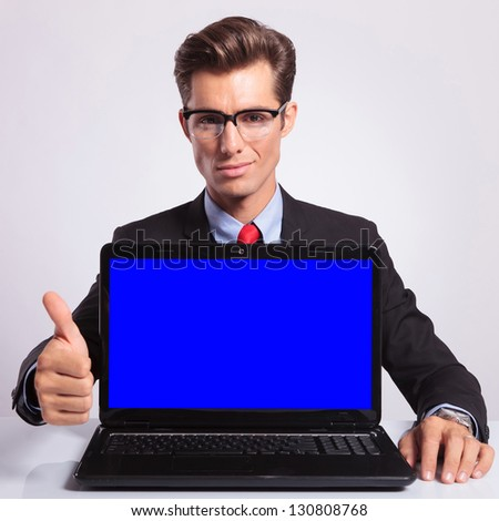 elegant young business man presenting a laptop and showing thumb up sign while looking at the camera with a reassuring expression - stock photo