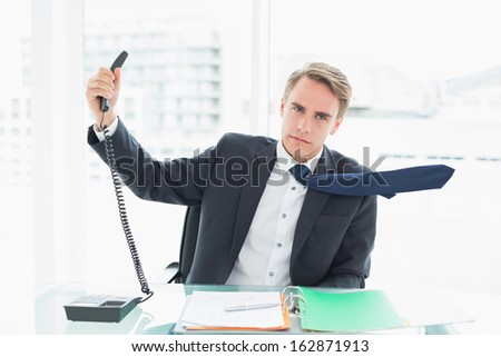 Elegant young businessman holding out phone at a bright office