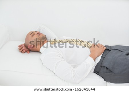 Elegant young businessman sleeping on sofa at home