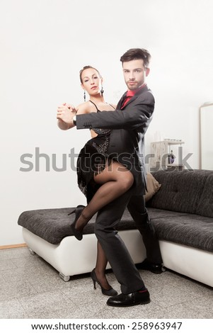 Elegant young couple dancing at home