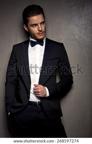 elegant young fashion man in a suit holding his hand on his jacket and looking at the camera.on black background - stock photo