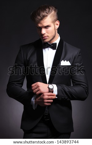 elegant young fashion man in tuxedo adjusting his cufflinks while looking at the camera. on black background - stock photo