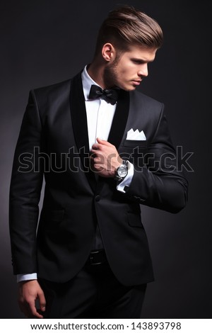 elegant young fashion man in tuxedo holding his hand on his jacket and looking to his side, away from the camera.on black background - stock photo