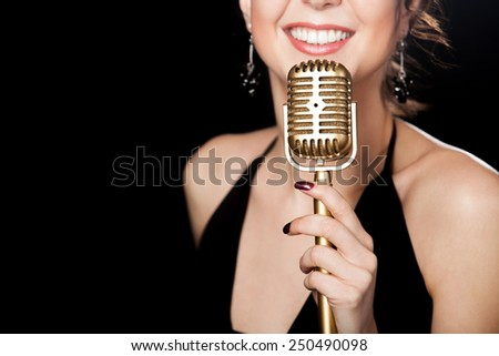 Elegant young female singer in black dress smiling holding golden vintage microphone, live performance, concert, unrecognizable person, close up, focus on mic, copy space - stock photo