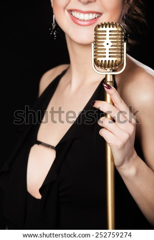 Elegant young female singer in black dress smiling holding golden vintage microphone, live performance, concert, unrecognizable person, close up, focus on mic - stock photo