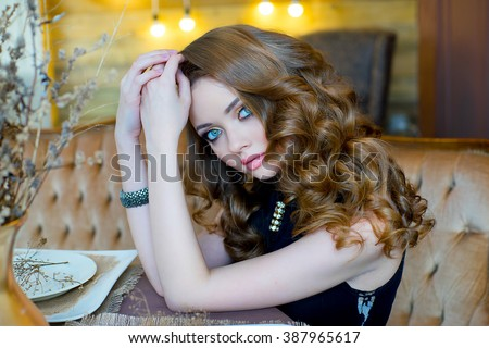 elegant young girl in a black evening dress, with a beautiful hairdress and with smart jewelry poses in an vintage interior. Fashion and beauty shooting.