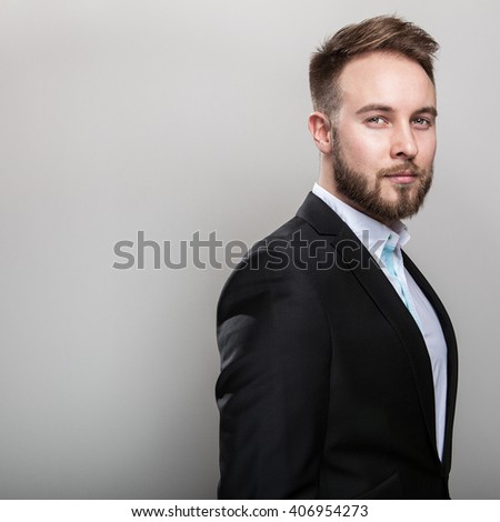 Elegant young handsome bearded man in classic black costume & white shirt.