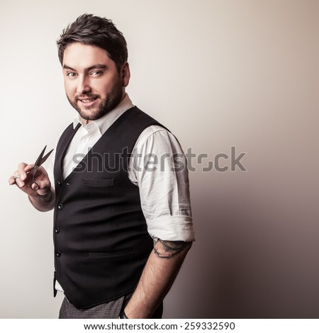 Elegant young handsome hairdresser with scissors in hand. Studio fashion portrait. - stock photo