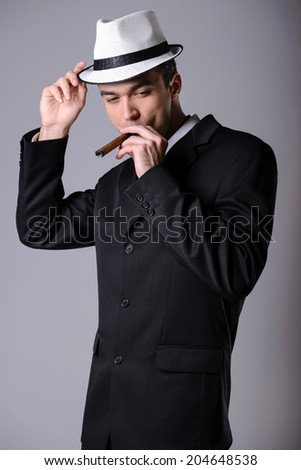Elegant young handsome man in a business suit with a cigar. Studio portrait of fashion.