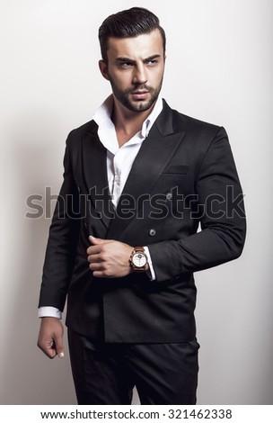 Elegant young handsome man in black classic costume. Studio fashion portrait.  - stock photo