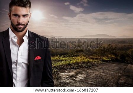 Elegant young handsome man in black costume pose on tropical view point.