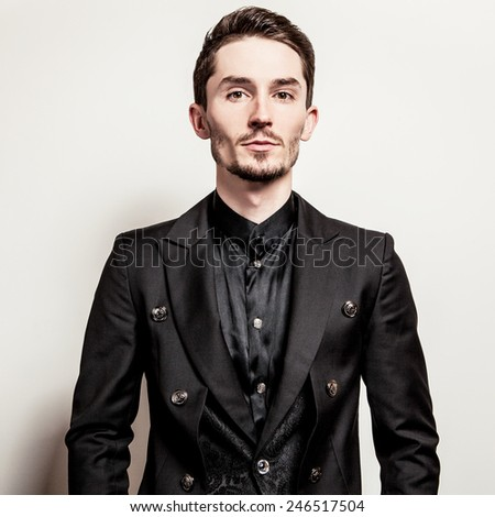 Elegant young handsome man in black costume. Studio fashion portrait.