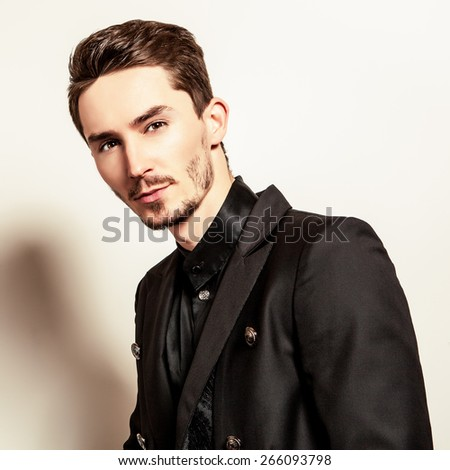 Elegant young handsome man in black costume. Studio fashion portrait. - stock photo