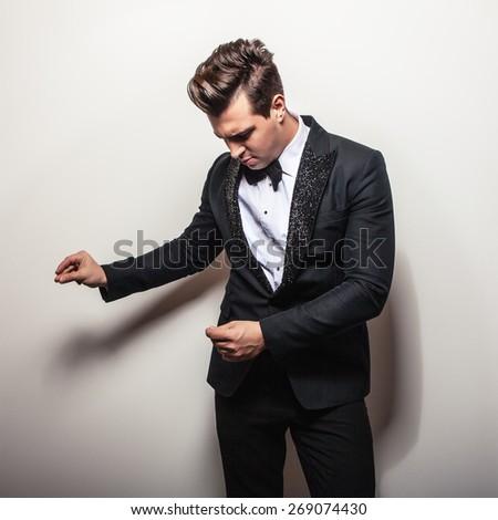 Elegant young handsome man in black luxury costume. Studio fashion portrait.  - stock photo