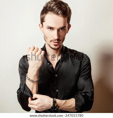 Elegant young handsome man in black silk shirt. Studio fashion portrait. - stock photo
