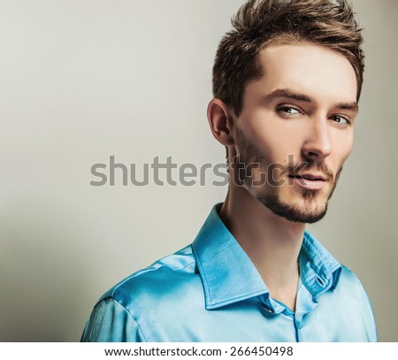 Elegant young handsome man in blue silk shirt. Studio fashion portrait.  - stock photo