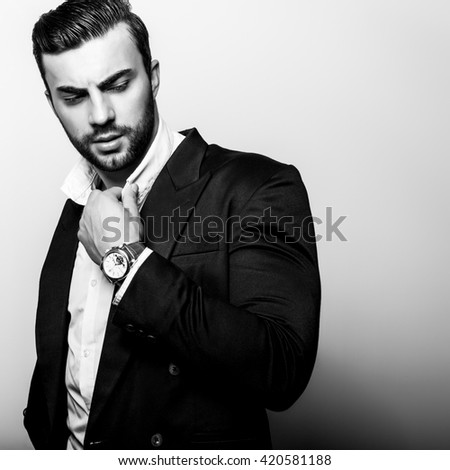 Elegant young handsome man in classic costume. Black-white studio fashion portrait. - stock photo
