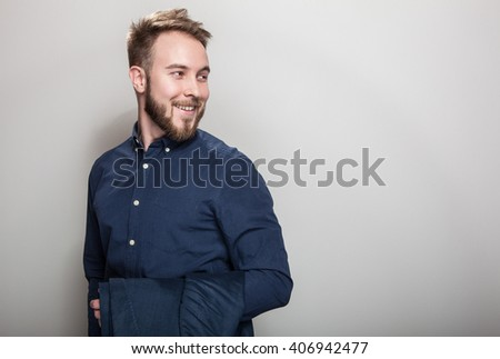 Elegant young handsome man in dark blue classic shirt and jacket on his shoulder. Studio fashion portrait.