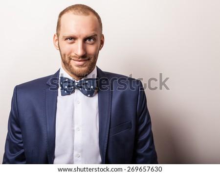 Elegant young handsome man in dark blue costume & bow tie. Studio fashion portrait. - stock photo