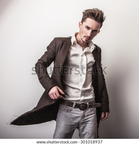 Elegant young handsome man in long stylish coat. Studio fashion portrait.