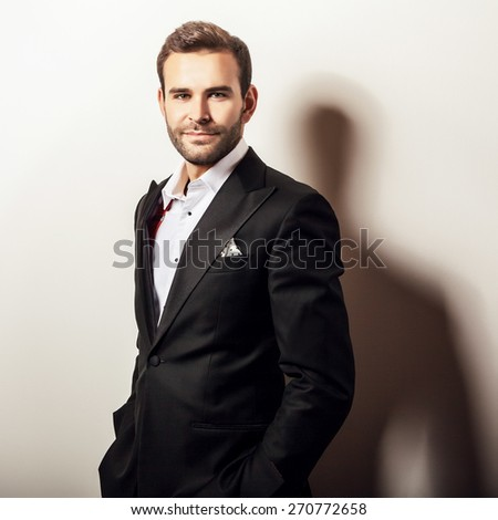 Elegant young handsome man in luxury black costume. Studio fashion portrait.  - stock photo
