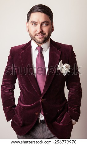 Elegant young handsome man in luxury velvet claret costume. Studio fashion portrait. - stock photo