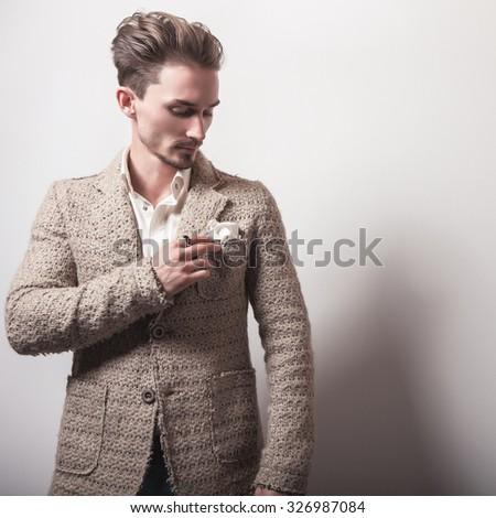 Elegant young handsome man in stylish beige costume. Studio fashion portrait.  - stock photo