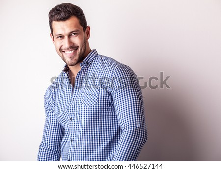 Elegant young handsome man in stylish blue shirt. Studio fashion portrait.