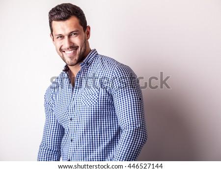 Elegant young handsome man in stylish blue shirt. Studio fashion portrait. - stock photo