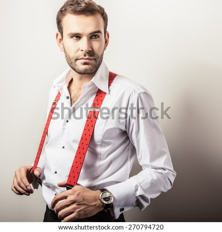 Elegant young handsome man in white shirt with red braces. Studio fashion portrait. - stock photo