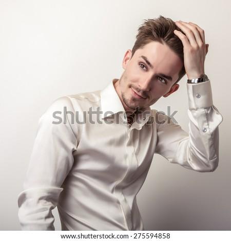 Elegant young handsome man in white silk shirt. Studio fashion portrait.  - stock photo