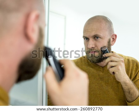 Elegant young handsome man making beard perfect