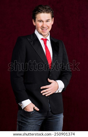 Elegant young handsome man on a dark red background - stock photo