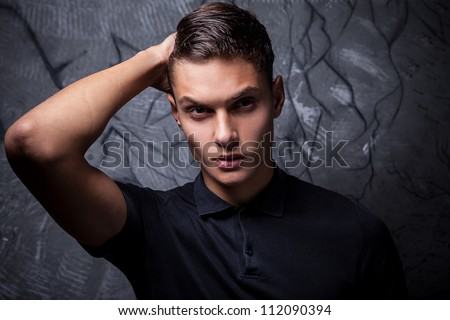 Elegant young handsome man on grunge background. Studio fashion portrait. - stock photo