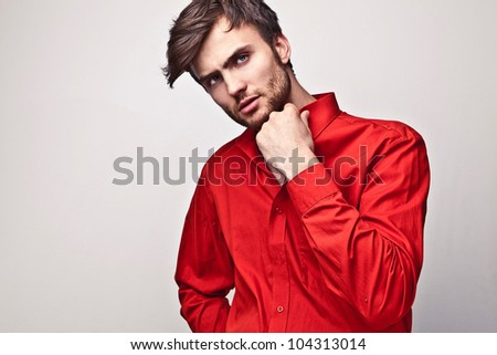Elegant young handsome man pose on red shirt. Studio fashion portrait.