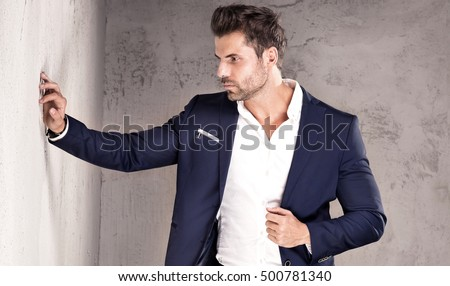 Elegant young handsome man posing in fashionable suit. Studio shot.