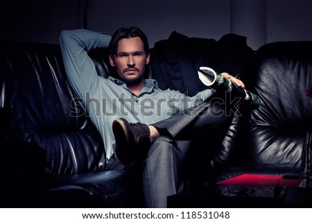 Elegant young handsome man sitting and resting - stock photo