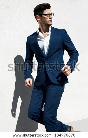 Elegant young handsome man wearing glasses and watchers. Running businessman in a suit - stock photo