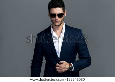 Elegant young handsome man wearing glasses and wathers. Studio fashion portrait. - stock photo
