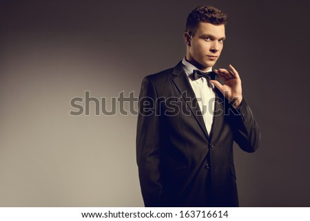 Elegant young handsome man wearing suit at studio fashion portrait  - stock photo