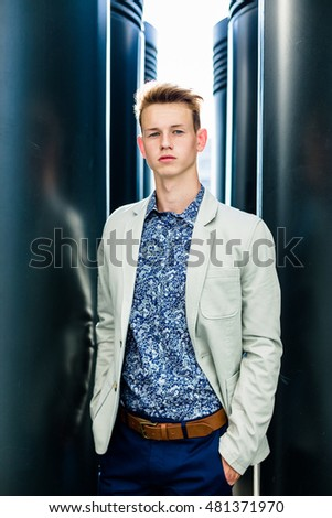 Elegant young handsome man wearing  white jacket and jeans near building