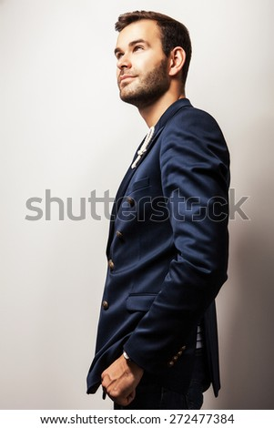 Elegant young handsome & positive man in dark blue jacket. Bright studio fashion portrait.  - stock photo