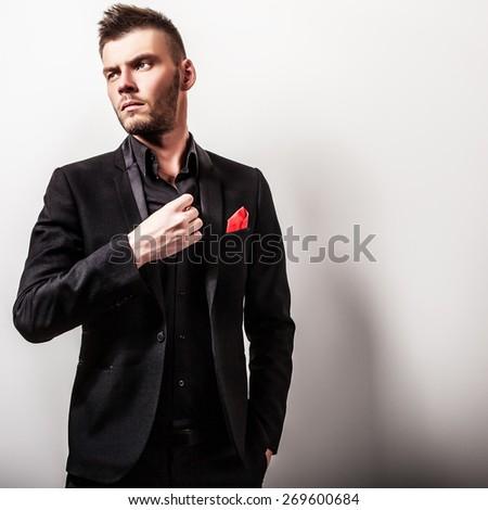 Elegant young handsome serious man in black costume. Studio fashion portrait.  - stock photo