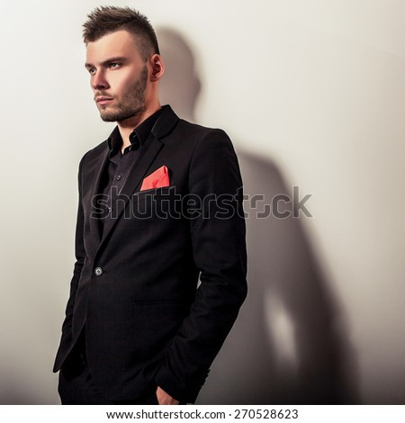 Elegant young handsome serious man in black costume. Studio fashion portrait.