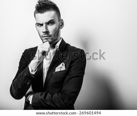 Elegant young handsome serious man in classic costume. Black-white studio fashion portrait.